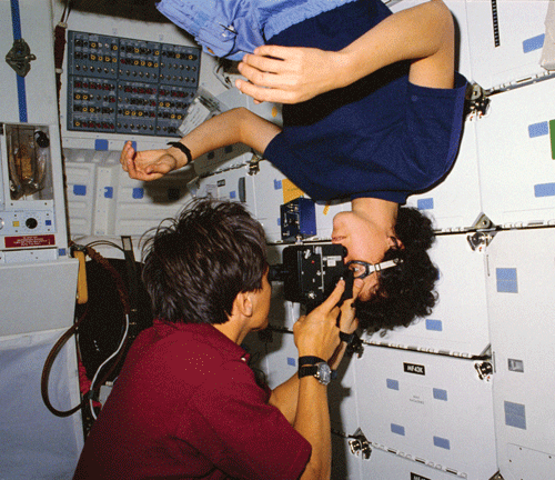 Astronaut Franklin R. Chang-Diaz performs an eye exam on astronaut Ellen S. Baker, MD, MPH, on the middeck of the Earth-orbiting space shuttle Atlantis.