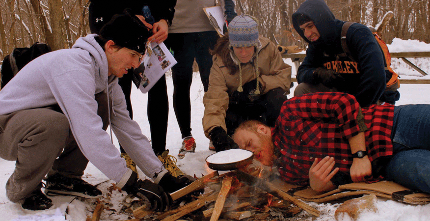 A team struggles to start a fire to melt snow during a frostbite scenario.